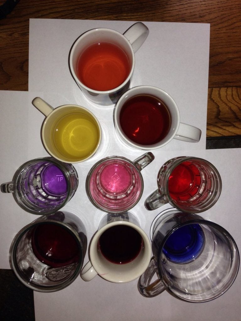 Pyramid of tea mugs from above, on white paper, with a rainbow of colours in them.
