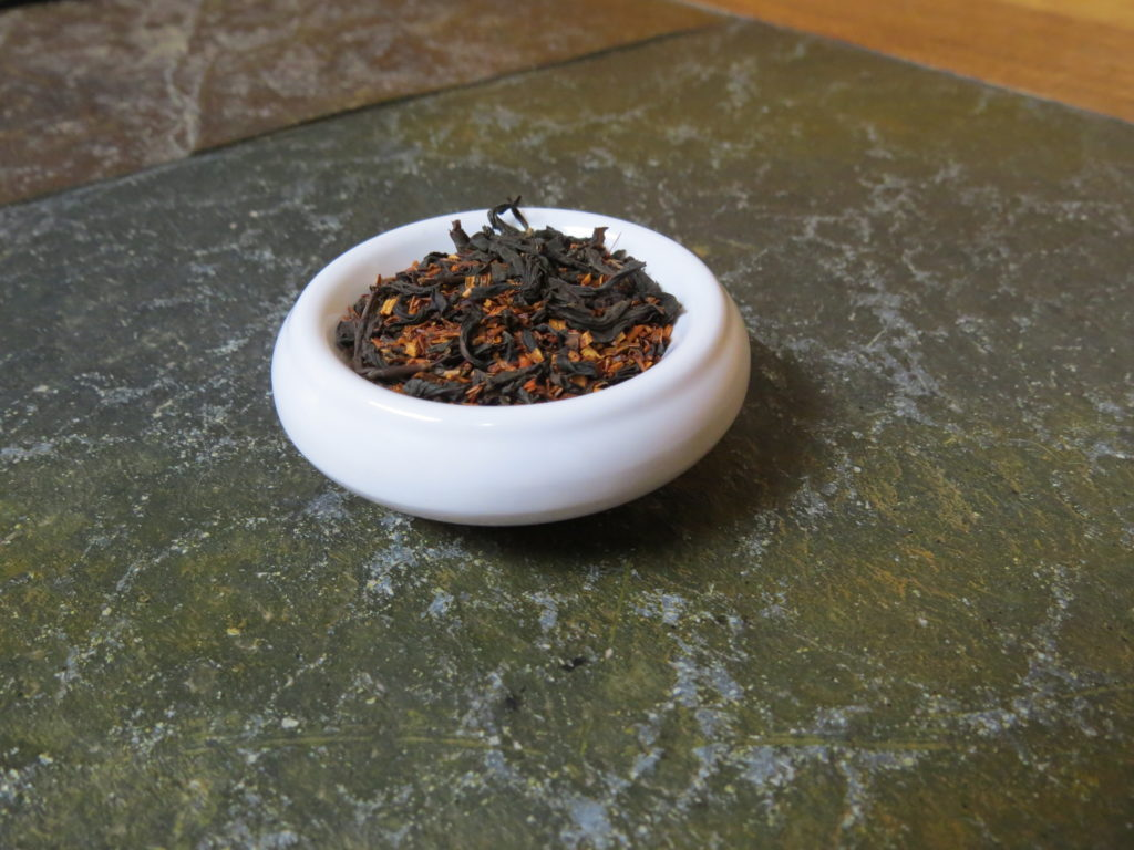 Small white bowl set on a green stone table filled with a blend of russian caravan tea and rooibos