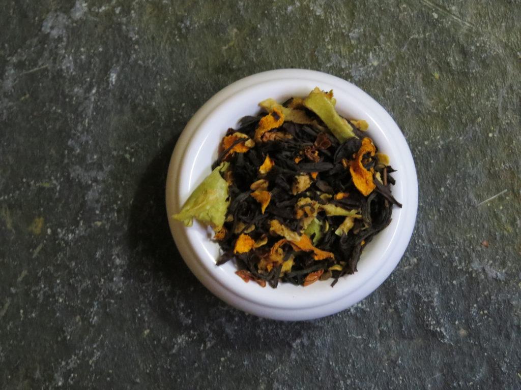Close-up image of a small white bowl full of a blend of black teas, chile flakes, dried turmeric bits, and pieces of dried green apple. It is set on a textured green stone.