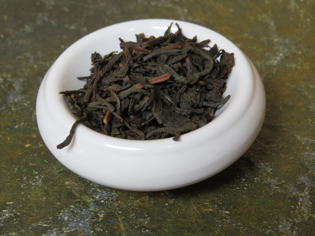 A small white bowl filled with a blend of black teas. It sits on a textured green stone table.