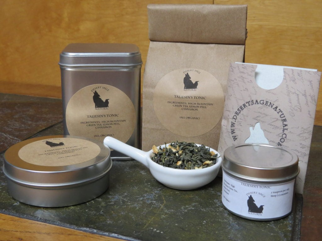 "A small white bowl full of a blend of green tea, cinnamon, and lemon peel, surrounded by an array of tea tins, a bag of tea, and a small paper packet that could hold a single teabag. The labels read: ""Taliesin's Tonic, Ingredients: High Mountain Green Tea, Lemon Peel, Cinnamon, (All Organic)."""