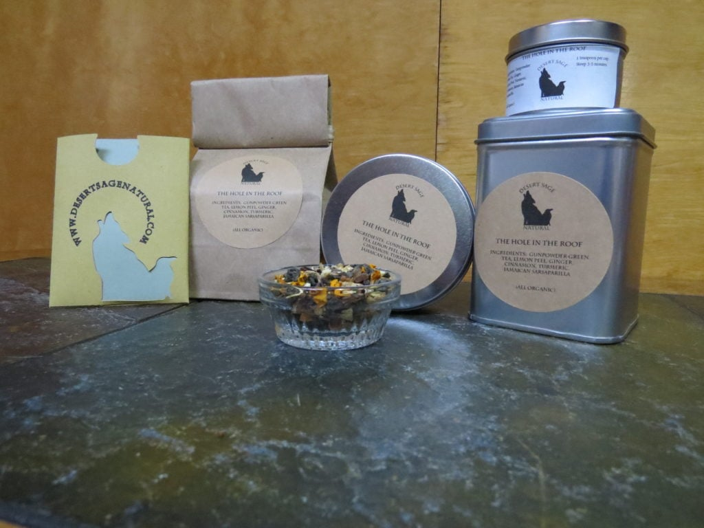 "A small bowl on a green textured stone table. The bowl is filled with a blend of gunpowder green tea, turmeric, ginger, cinnamon, sarsaparilla, and lemon peel. Behind the bowl are 3 tins in various shapes and sizes, a bag of tea, and a cardboard packet with the Desert Sage Natural logo, of a size to hold a single teabag. The labels read: ""The Hole in the Roof, Ingredients: Gunpowder Green Tea, Ginger, Lemon Peel, Turmeric, Cinnamon, Jamaican Sarsaparilla, All Organic"""