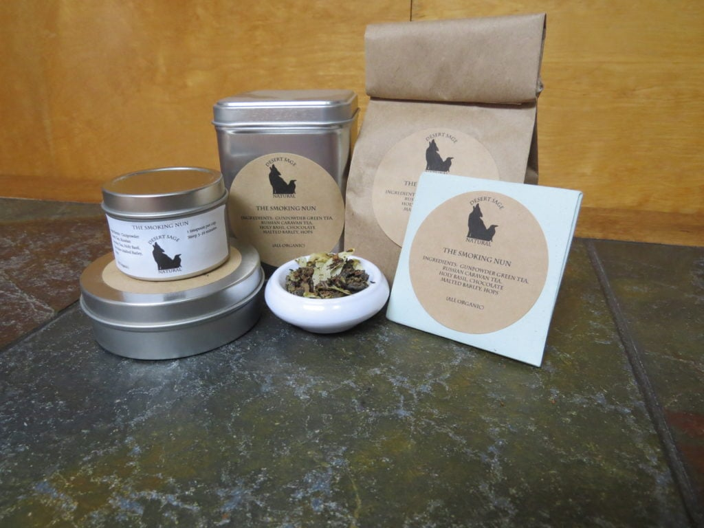 "A small white bowl full of a blend of gunpowder green tea, russian caravan tea, holy basil, hops, and chocolate malted barley. It is surrounded by an array of tea tins, a bag, and a small origami packet of a size to hold a single teabag. The labels read ""The Smoking Nun, Ingredients: Gunpowder Green, Russian Caravan, Holy Basil, Chocolate Malted Barley, Hops, (All Organic)"""