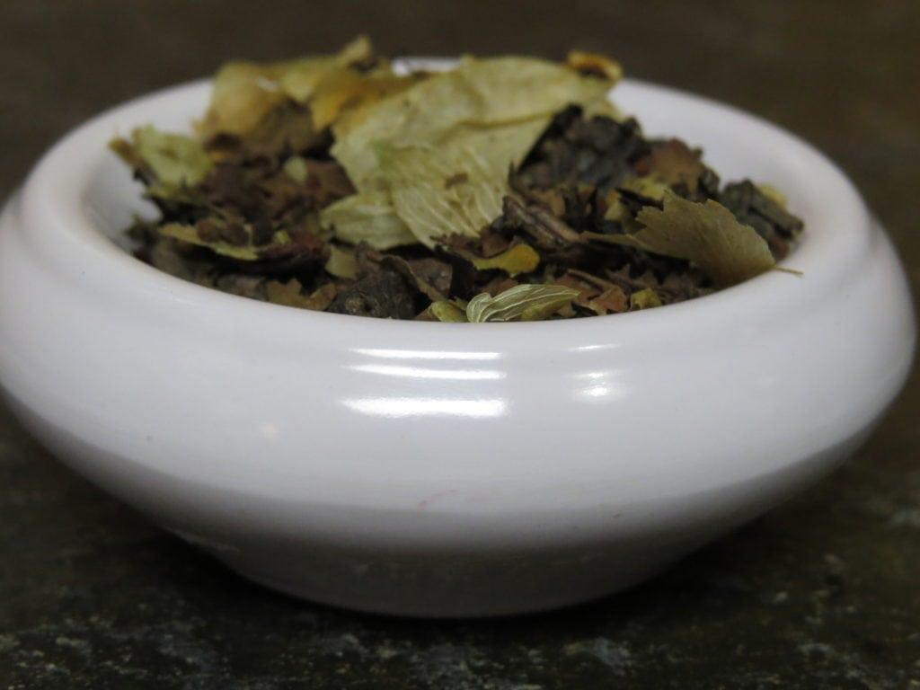 A very close-up image of a small white bowl full of gunpowder green tea, russian caravan tea, hops, holy basil, and barley.