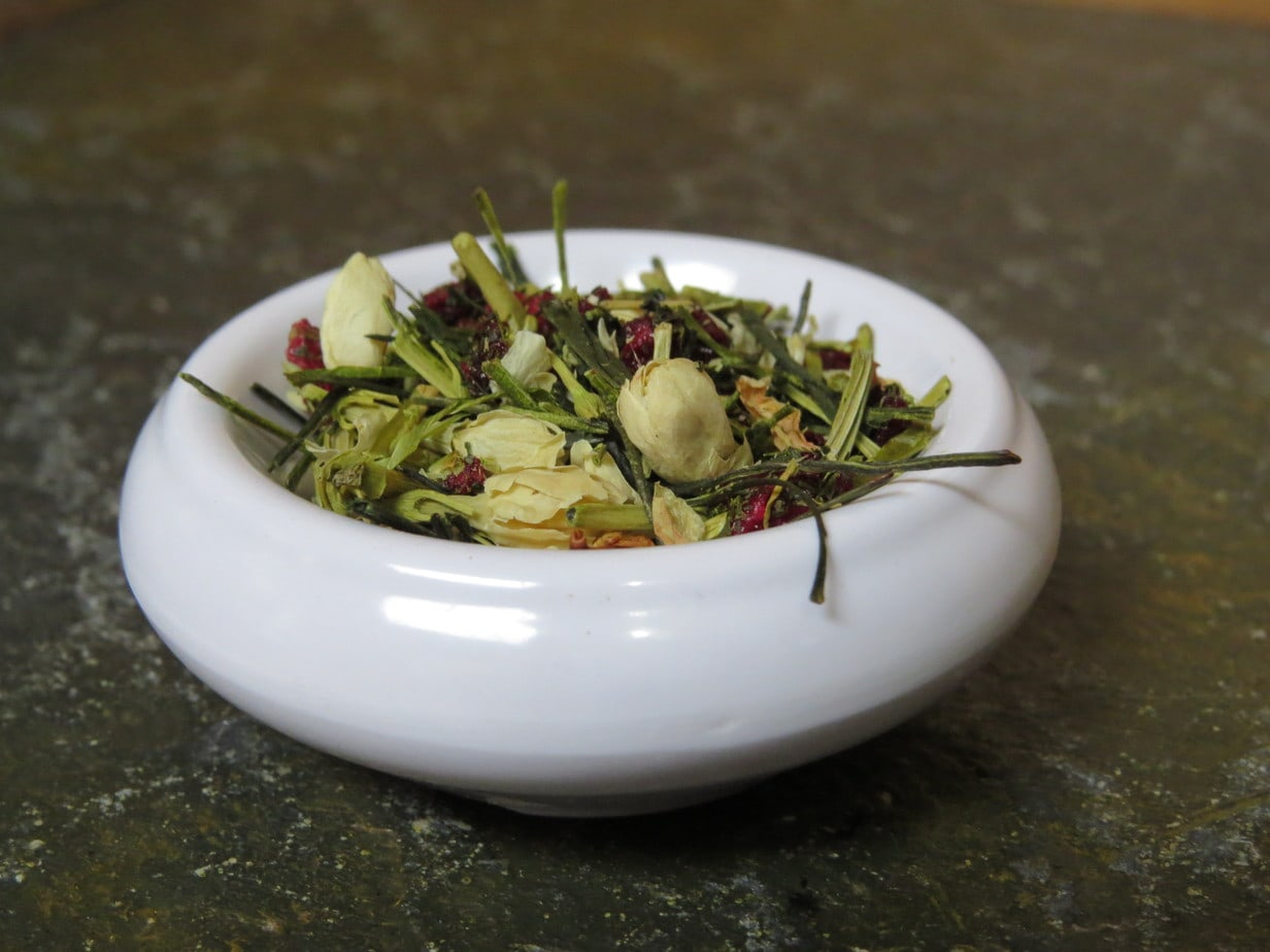 A closeup image of a small white bowl on a green textured stone table. The bowl is full of a blend of green Kukicha tea, freeze dried cherries, and jasmine flowers.