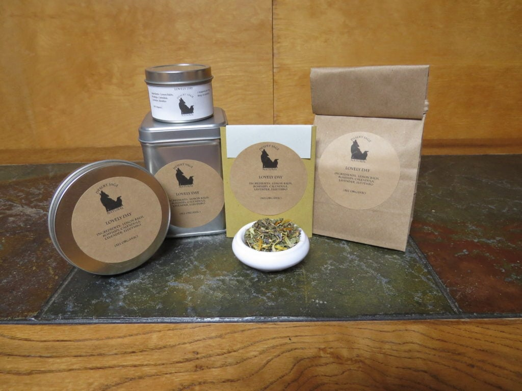 "A small white bowl full of a blend of lemon balm, rosehips, calendula, lavender, and eleuthro. It is surrounded by a variety of tea tins, a bag of tea, and a small rectangular packet that could hold a single teabag. The labels read ""Lovely Day"" and have the list of ingredients, also noting that they are all organic."