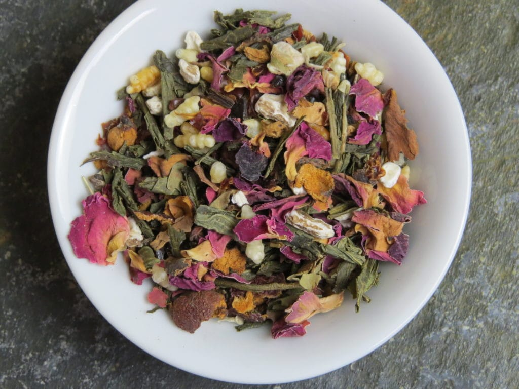 A small white bowl full of a blend of genmaicha green tea, hawthorn, dandelion, rosehips, and rose petals. The image is quite zoomed in, allowing you to see all the details of the tea.
