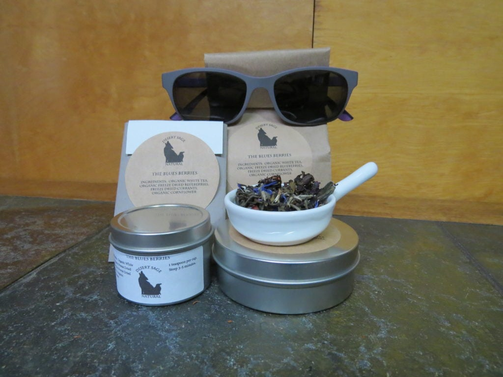 "Two tins, one tall and thin, one short and wide, next to each other. The thinner tin has a small white bowl with a blend of white tea, blueberries, currants, and cornflower. Behind those are a rectangular packet that would hold a teabag, and a bag of tea. The labels read: ""The Blues Berries, Ingredients: Organic White Tea, Organic Freezedried Blueberries, Freezedried Currants, and Organic Cornflower."" The bag of tea is wearing a pair of grey sunglasses."