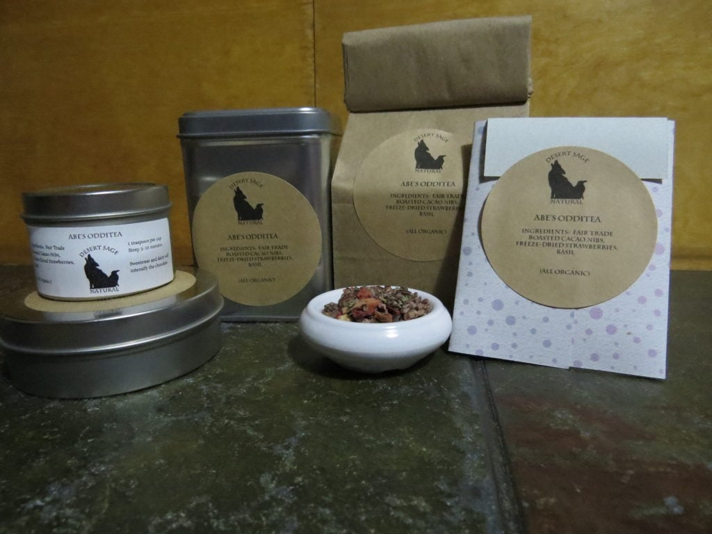 "A small white bowl full of a blend of cacao nibs, freeze dried strawberries, and basil. Arrayed around it are a variety of tea tins, a bag of tea, and a small rectangular packet that could hold a teabag. The labels read: ""Abe's OddiTea, Ingredients: Fair Trade Roasted Cacao Nibs, Freeze Dried Strawberries, Basil, (All Organic)"""