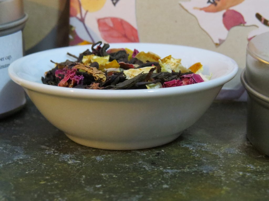 A small white bowl filled with a blend of black tea, rose petals, and lime peel. In the background you can see the edges of tea tins and tea packets.