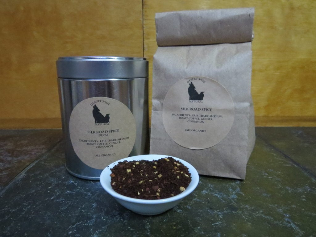 "A small white bowl full of a blend of coffee, cinnamon, and ginger. Behind it stand a bag and a tin. The labels read ""Silk Road Spice, Ingredients: Fair Trade medium Roast Coffee, Cinnamon, and Ginger (All Organic)"" One is marked as caffeinated, the other as decaf."
