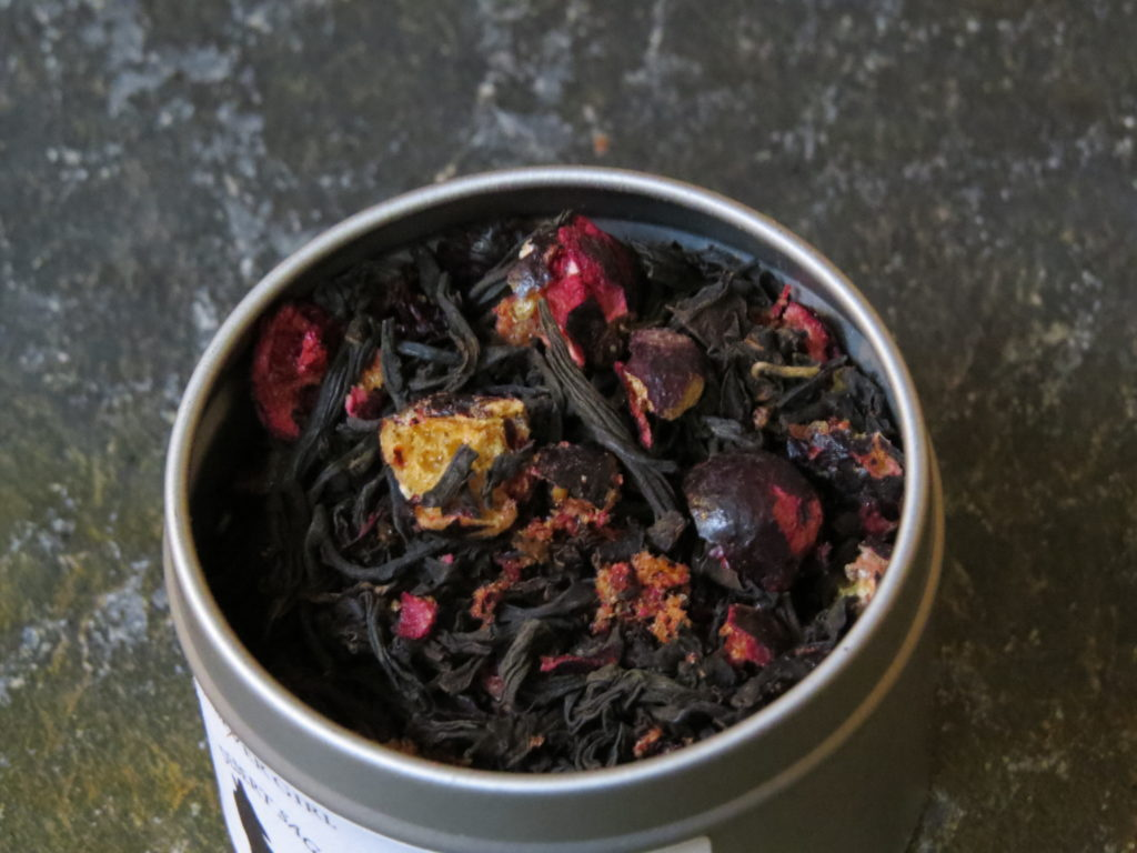 Closeup of a small metal tin filled with a blend of black tea and freeze dried currants.