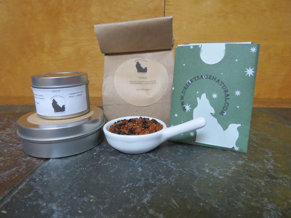 "A small white bowl full of a combination of rooibos, dried elderberries, and cinnamon. it is surrounded by two small circular tea tins, in different sizes, a bag of tea, and a small rectangular packet with a cutout of the Desert Sage Natural logo that could hold a single teabag. The labels read ""Syzygy, Organic Ingredients: Rooibos, Elderberries, Cinnamon"""