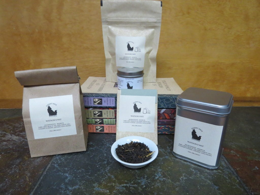 """A small white bowl filled with a blend of black teas. Surrounding it are a stack of the complete set of Sherlock Holmes novels, as well as a variety of tea containment objects. The labels read: """"Watson's Wit, Organic Ingredients: Keemun, Earl Grey, Lapsang Souchong, and Golden Yunnan."""""""