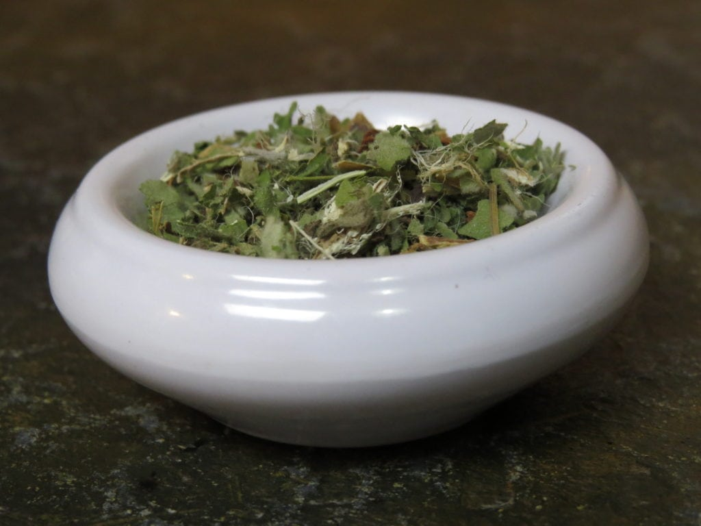 Small white bowl full of licorice, cinnamon, sage, and marshmallow leaf and root. The image is in close on the tea and bowl, though you can see the green stone of the table underneath.
