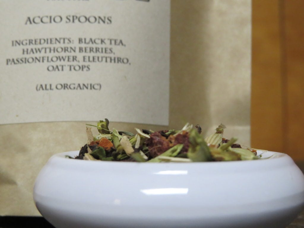 "A closeup image of a small white bowl full of a blend of passionflower, eleuthro, oat tops, hawthorn berries, and black tea.  Behind it is the slightly blurry label that indicates what the tea is.  It calls it ""Accio Spoons,"" lists the ingredients, and indicates that they are all organic."