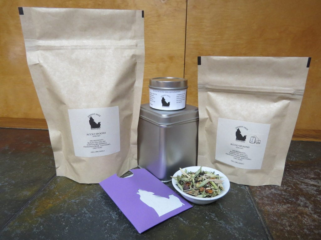 "A small white bowl of tea full of herbs.  Around it are arrayed a variety of tea containment objects - tins and bags, and a small rectangular packet that could hold a single teabag.  They are labeled ""Accio Spoons (Decaffeinated), Ingredients:Black Tea, Hawthorn Berries, Passionflower, Eleuthro, Oat Tops (All Organic)"""