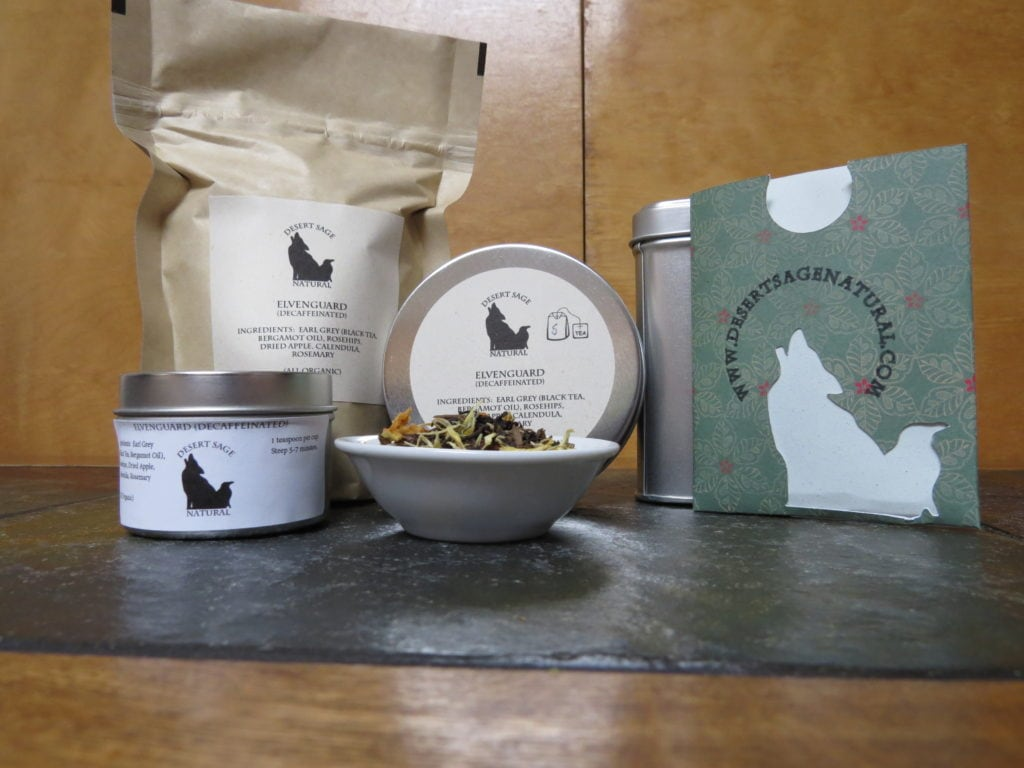 """A small white bowl set on a textured green marble tabletop, the light catching the tea tin just behind so the bowl has a halo of light.  The bowl is full of a mix of flowers, fruit, and tea.  To the left of the bowl is a small tea tin, to the right a rectangular packet with the Desert Sage Natural Raven and Coyote logo as a cutout and www.desertsagenatural.com ringing the coyote's head.  A bit further back behind is a large bag of tea.  The labels read:  """"Elvenguard (Decaffeinated), Ingredients:  Earl Grey, Rosehips, Calendula, Dried Apple, Rosemary, (All Organic)"""""""