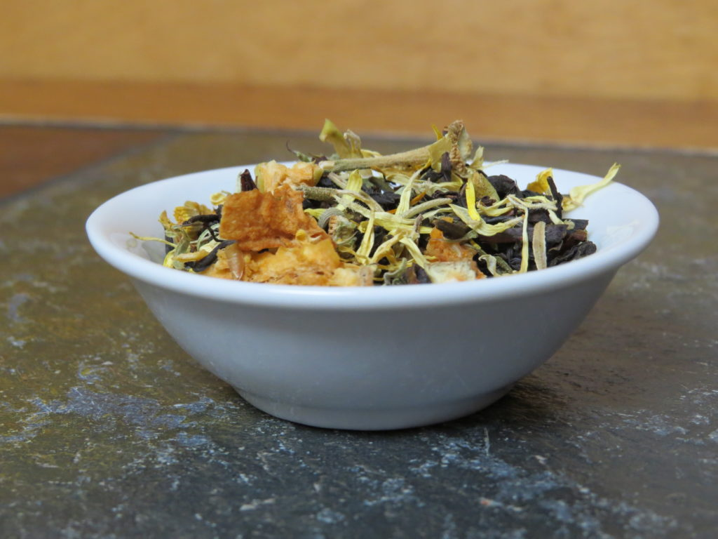 A small white bowl sitting on a green textured marble table.  The bowl is full of a blend of black tea, rosehips, calendula, dried apple, and rosemary.