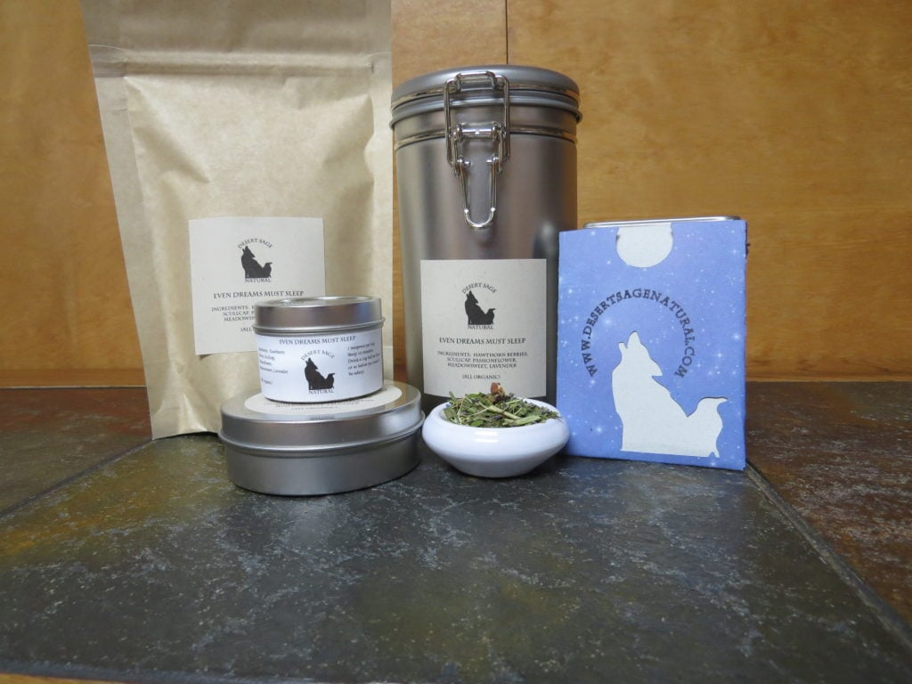 """A small white bowl on a textured marble table.  The bowl is full of a blend of lavender, hawthorn berries, and green herbs.  To the left side are two small tins, stacked, one thinner and taller than the other.  To the right is a rectangular packet with the Desert Sage Natural logo and website, of a size where it could hold a teabag.  Behind the bowl is a large bag and a large tin.  The labels on things read:  """"Even Dreams Must Sleep, Ingredients:  Hawthorn Berries, Scullcap, Passionflower, Meadowsweet, Lavender, (All Organic)"""""""