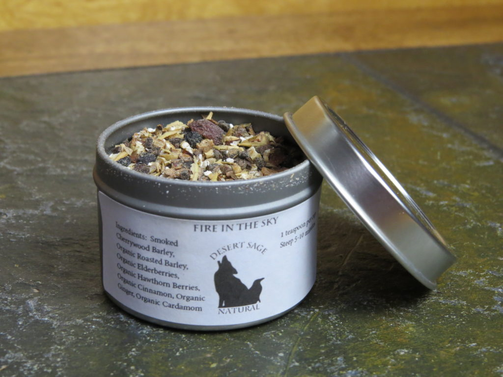 """A small metal tea tin, set on a textured green stone table.  The tin is open, the lid propped up at an angle on one side of it, and there is a slight dusting of barley and spice around the rim of the tin.  The label reads  """"Fire in the Sky, Ingredients:  Smoked Cherrywood Barley, Organic Roasted Barley, Organic Elderberries, Organic Hawthorn berries, Organic Cinnamon, Organic Ginger, Organic Cardamom"""""""
