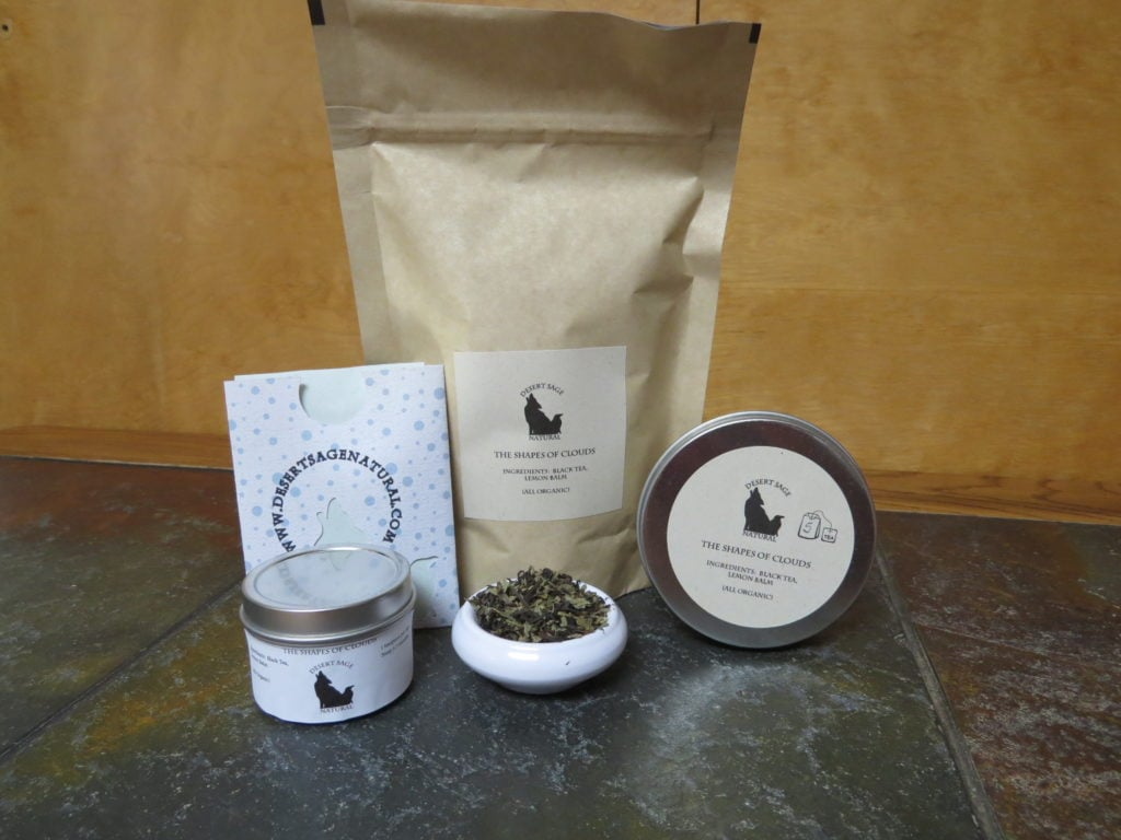 "A small white bowl of tea filled with a blend of lemon balm and black tea.  To either side are tea tins, behind it a large bag and a small rectangular packet that looks as if it could hold a teabag.  The labels read: ""The Shapes of Clouds, Ingredients:  Black Tea, Lemon Balm, (All Organic)."