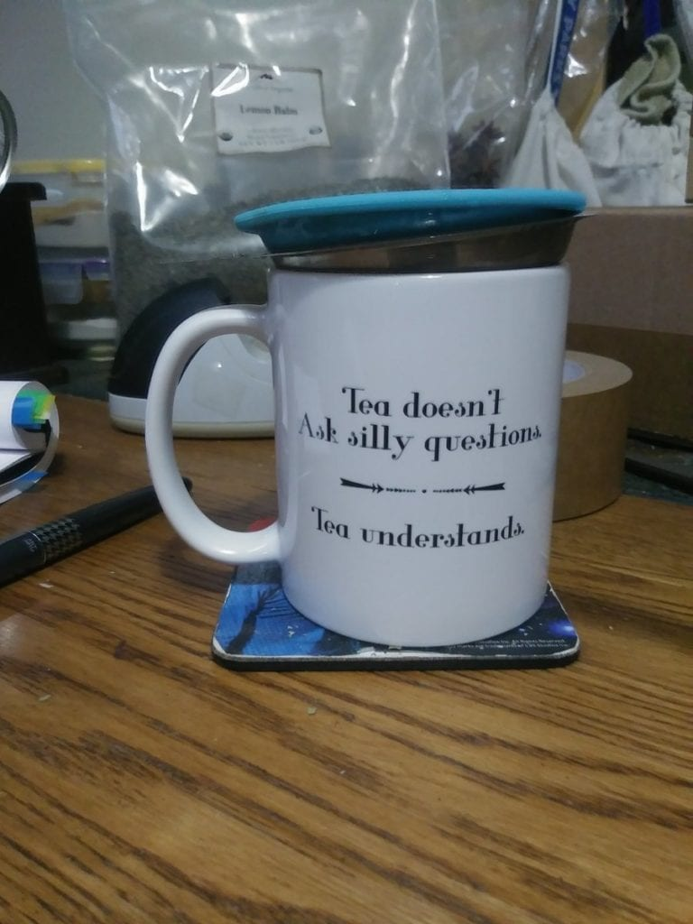 "A white tea mug with the words: ""Tea doesn't ask silly questions, tea understands,  In it is a tea strainer with a blue lid.  There is a grey pilot fountain pen to the left, a large bag of lemon balm behind, and there is a part of a roll of packing tape behind the mug, too."