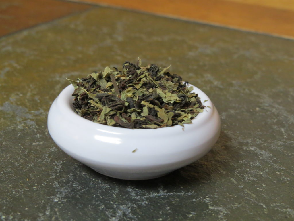 A small white bowl almost overfilled with a blend of black tea and lemon balm.  It is set on a marble and wood table, the image pulled in close on the tea.