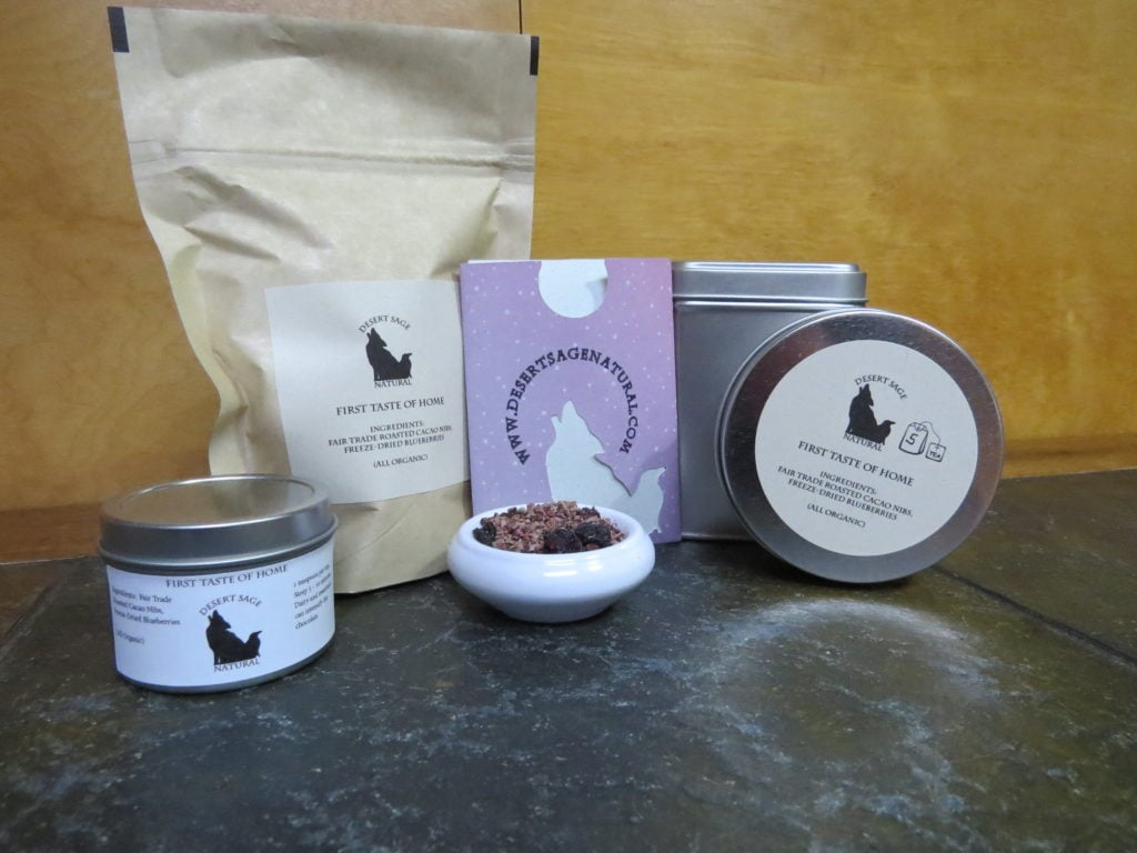"A bag of tea, two circular tea tins, a taller square tin, and a teabag packet arrayed around a small white bowl full of a combination of cacao nibs and blueberries.  The labels read ""First Taste of Home"" and list those two ingredients, as well as stating that they are both organic."
