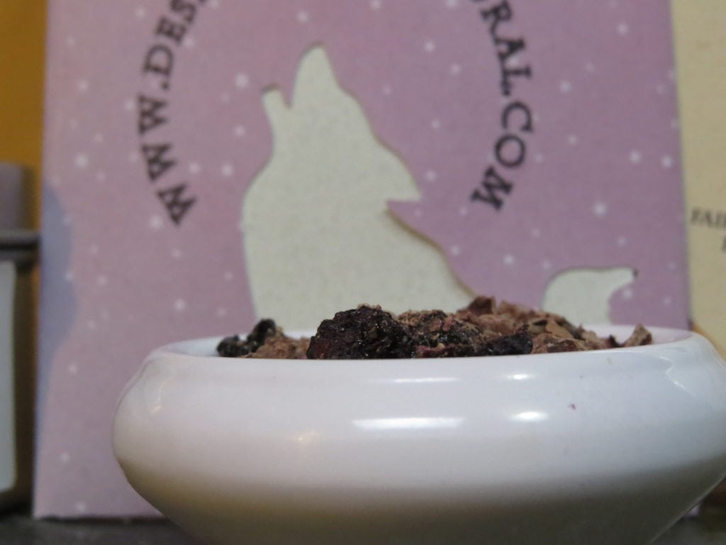 Closeup image of a small white bowl filled with ground cacao nibs and freeze dried blueberries.  Behind it there is a light pinkish purple packet, with the raven and coyote logo as a cutout, and part of the web address for Desert Sage Natural.
